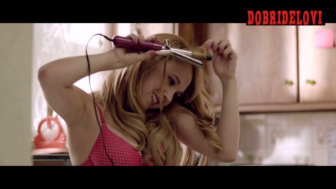 Juno Temple in the kitchen with a curling iron scene from The Brass Teapot