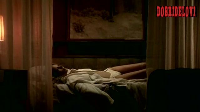 Deborah Kara Unger laying in bed in white lingerie scene from Paranoia: 1.0